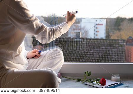 A Girl Sits On The Windowsill And Writes Something On The Window Glass, In The Morning
