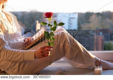 A Young Girl Sits On A Windowsill In Her Hand A Red Rose, At Sunset