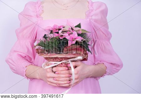 Young Girl In A Pink Dress Holding A Bouquet Of Christmas Flowers On A White Background