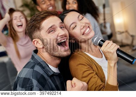 Bring The Song To Life. Young Excited Couple Or Friends Holding Microphone And Singing Together Whil
