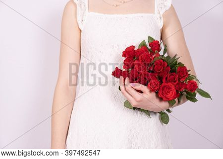 A Young Girl In A Dress Holding A Bouquet Of Red Roses On A White Background