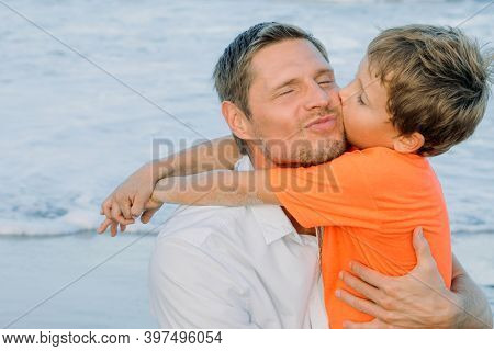 Cute Child Boy Hugs And Kisses His Father Tightly On Sea Background. Concept Of A Loving And Friendl