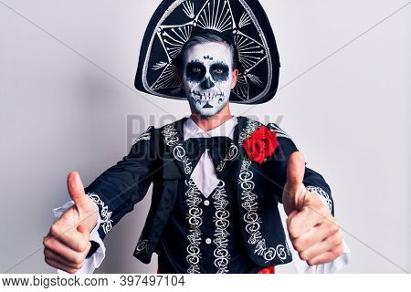 Young man wearing mexican day of the dead costume over white approving doing positive gesture with hand, thumbs up smiling and happy for success. winner gesture.