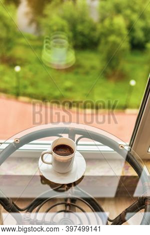 Cup Of Coffee On Balcony With Nature View Behind. White Cup With Coffee On The Balcony By The Window