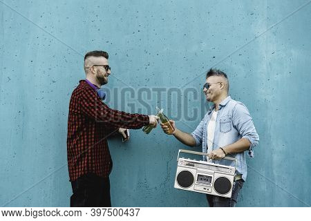 Cool Men Toasting Beer Outdoor Against A Blue Wall Background While Listening Music With A Vintage B
