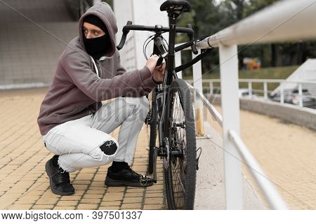 Caucasian Male Thief In Balaclava And Hood Breaks The Lock On A Bicycle In The Street During The Day