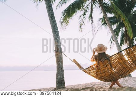 A Young Woman In Straw Hat Sitting In A Hammock Swinging Between A Palm Trees On The Overseas Island