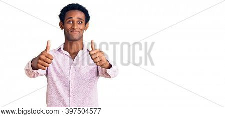 African handsome man wearing casual pink shirt approving doing positive gesture with hand, thumbs up smiling and happy for success. winner gesture.