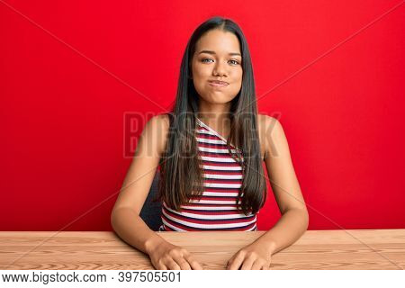 Beautiful hispanic woman wearing casual clothes sitting on the table puffing cheeks with funny face. mouth inflated with air, crazy expression.