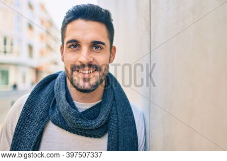 Young hispanic man smiling happy wearing scarf leaning on the wall at the city