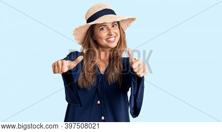 Middle age hispanic woman wearing summer hat approving doing positive gesture with hand, thumbs up smiling and happy for success. winner gesture.