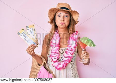 Middle age hispanic woman wearing hawaiian lei holding boarding pass and cocktail puffing cheeks with funny face. mouth inflated with air, catching air.