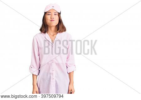 Young beautiful chinese girl wearing sleep mask and pajama puffing cheeks with funny face. mouth inflated with air, crazy expression.