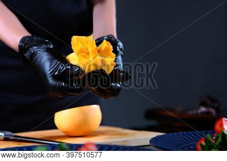 Ripe Mango In The Hands Of The Chef. The Chef Cuts Mango. Preparation Of Mango And Octopus Salad. Un