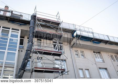 Building With Scaffolding Under Going Renovation. Building With Scaffold And Debris Chute . Construc