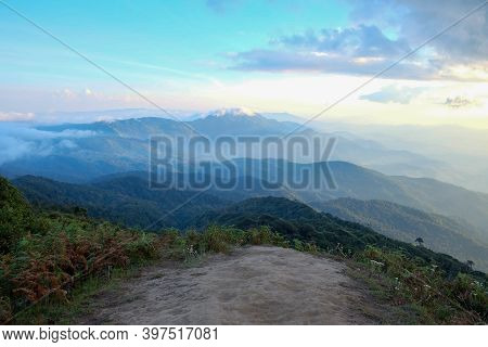 Blurred White Fluffy Clouds Blue Sky In Bright Day  Over High Mountain With A Line Of Tropocal Trees