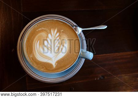 A Blue Cup Of Hot Latte Coffee With Wooden Spoon On The Wooden Coffee Cafe,latte Art