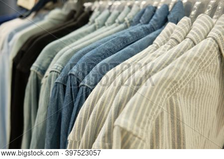 Different Casual Men Shirts Hang On Hanger Racks At Store