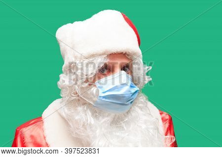Santa Claus Wears A Paper Face Mask Due To Covid-19. Coronavirus Is Dangerous And Is World Wide. Be