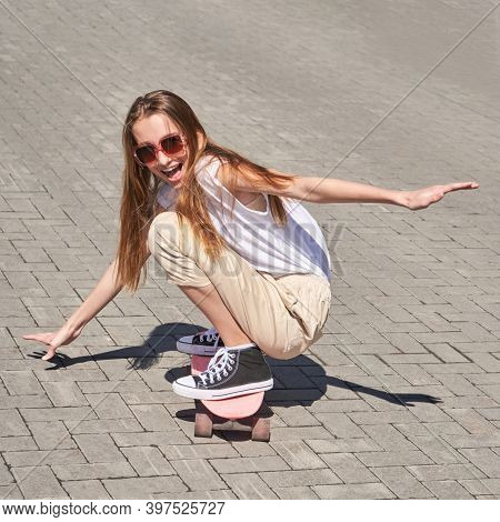 Young Woman Show Skateboard Deck. Pink Color. Sun Shade. High Quality Photo. Skatepark Equipment. Te