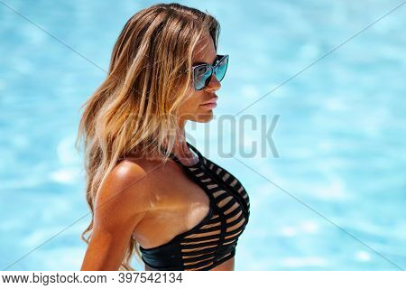 Beautiful Sexy Blonde Woman With Long Hair And Tanned Body Wearing Black Swimsuit And Sunglasses Pos