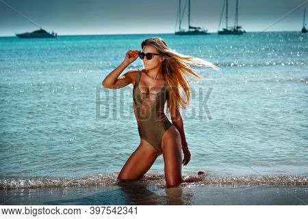 Portrait Of Beautiful Sexy Smiling Blonde Woman With Long Hair And Tanned Body Wearing Gold Swimsuit