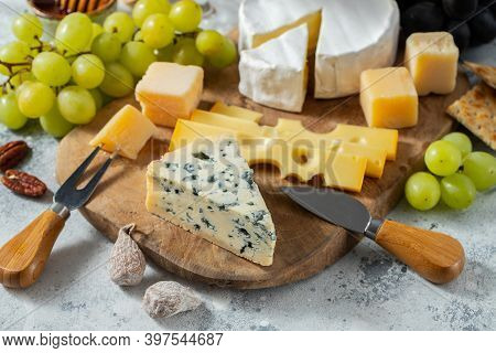 Tasting Cheese Dish On A Wooden Plate. Food For Wine And Romantic Date, Cheese Delicatessen On A Lig