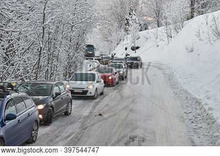 Cars after a blizzard on an alpine road, congestion with line of vehicles waiting to pass