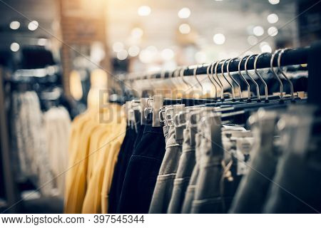 Shopping In Store. Clothes On Hangers In Shop For Sale. Blur Background. Fashionable Clothes In A Bo