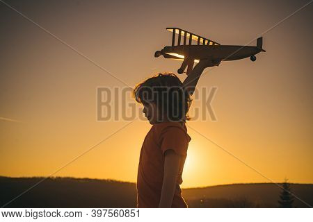 Child Dreaming. Kid Pilot Aviator With Airplane Dreams Of Traveling In Summer In Nature At Sunset