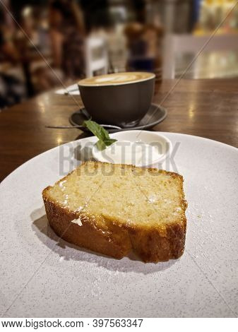 A Slice Of Lemon Cake And A Small Pot Of Yoghurt On A Table At A Coffee Shop