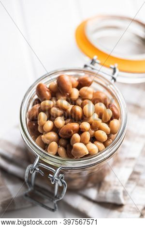 Mix of legume beans and chickpeas with sauce in jar.