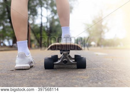 Close Up Rear View Asian Women Leg On Surf Skate Or Skate Board In Outdoor Park. Closeup Leg Wear Wh