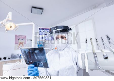 Patient Pov In Dental Office Looking At Dentist Holding Radiography Dressed In Protective Gear Durin