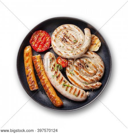Hot spicy grilled sausages on plate. Isolated on white background. Top view flat lay