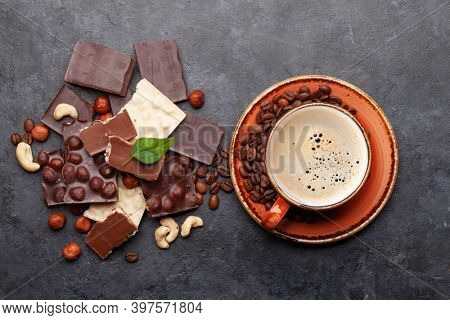 Various chocolate pieces, coffee and nuts on stone table. Top view flat lay