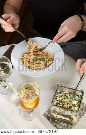 Woman Eating Italian Chicken Pasta Served In A Cafe