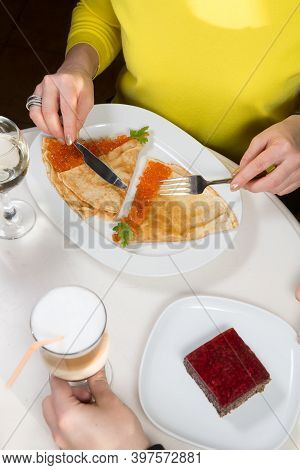 People Eating Crepes With Red Caviar In A Restaurant