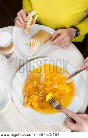 People Eating Salmon Roll And Crepes For Breakfast At A Cafe