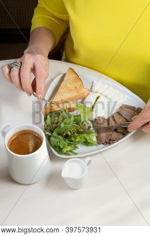 Woman Having Poached Egg With Salad For Breakfast In A Cafe