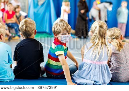 Children Watching Theater Or Concert At School. Little Kid Boy Wear Medical Mask As Protection From