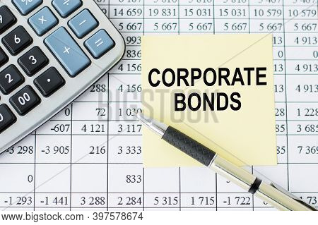 On A Desk Calculator, Pen And Note Paper With Text Corporate Bonds On The Numbers Background