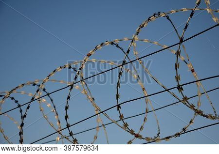 Razor Barbed Wire On A Fence Against The Sky Rolled Into Circles And Spirals Protects Objects And Bo
