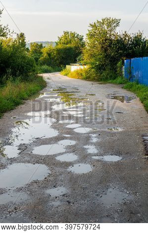 Bad Ground Road After Rain. Puddle On Way. Pot Hole Or Pothole Image With A Dirty Water Puddle As A