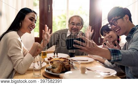 Happy asian multigenerational family of dad mom daughter girl and grandfather taking selfie together before eating lunch together at home.  Happy family engagement togetherness concept.