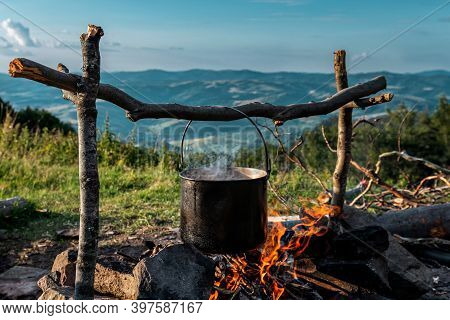 On The Fire Cauldron. Preparing Food At The Campsite. View Of The Mountains From The Campsite.