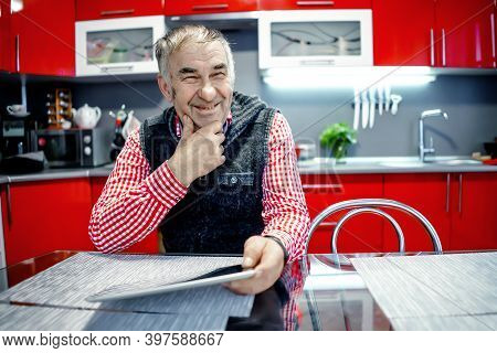 An Elderly Man With A Tablet Smiles While Sitting At A Table.