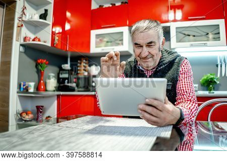 An Elderly Man With A Tablet Communicates With Relatives And Waves His Hand.
