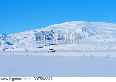 Route 1, Iceland - 5 2020: Typical Icelandic Winter Landscape With Mountains Under Snow And Blue Sky