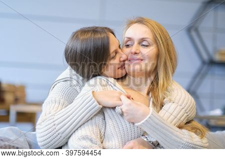 Beautiful Family Of Mother And Daughter Together, Hugging And Kissing At Home. Senior Mom And Her Ad